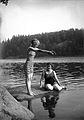 Två kvinnor i baddräkt på sten vid vattnet. Den ena gör sig beredd att dyka i - Nordiska Museet - NMA.0034226.jpg