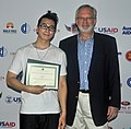 U.S. Ambassador David Shear presents Vietnamese rapper, Karik, with a certificate of appreciation for taking parting in the MTV EXIT concert against human trafficking and exploitation (7285435852).jpg