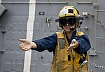 U.S. Navy Boatswain's Mate 3rd Class Stephanie Ramsey simulates directing an aircraft during a crash and salvage drill aboard the guided missile destroyer USS William P. Lawrence (DDG 110) Aug. 30, 2013, in 130830-N-ZQ631-001.jpg