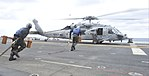 U.S. Sailors aboard the amphibious assault ship USS Bataan (LHD 5) run to place chocks and chains on an MH-60 Seahawk helicopter carrying two Turkish mariners recovered by Bataan search and rescue in the Aegean 140308-N-AO823-025.jpg