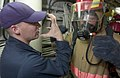 US Navy 060526-N-9851B-005 Damage Control Training Team (DCTT) member, Hospital Corpsman 1st Class Carmon Whatley, explains to Engineman Fireman Sean McCarty how to get a proper seal on his Self Contained Breathing Apparatus (S.jpg