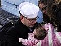 US Navy 061206-N-1831S-378 Boatswain's Mate Seaman David Rumohr holds his newborn child after returning from deployment aboard the amphibious transport dock USS Nashville (LPD 13).jpg