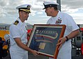 US Navy 080114-N-5476H-076 Arleigh Burke-class guided-missile destroyer USS Russell (DDG 59) Command Master Chief Julio Diaz presents Cmdr. Brad Cooper, commanding officer of Russell, with the ship's commissioning pennant durin.jpg