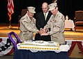US Navy 080705-N-9167V-008 Vice Adm. William Gortney, left, U.S. Ambassador to the Kingdom of Bahrain, J. Adam Ereli, center, and Vice Adm. Kevin Cosgriff, right, perform the traditional cake-cutting following a change-of-comma.jpg