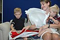 US Navy 080725-N-7138C-018 Lt. Cmdr. Jeannie Groeneveld and her two sons open a package of quilts given to her family by the.jpg