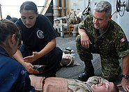US Navy 080926-N-9134V-043 Canadian Army Capt. Rory MacDonald comforts a simulated victim
