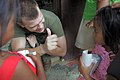 US Navy 090421-A-0759M-063 Hospital Corpsman 3rd Class Piotor Juchniewicz, gives a thumbs up while handing out medication during a medical civic action project supporting Balikatan 2009 at Nakar Elementary School.jpg