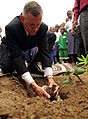 US Navy 090610-F-3682S-401 U.S. Navy Captain Mark Sparling, from Combined Joint Task Force-Horn of Africa plants a memorial mango tree during the Ziwani Primary School Renovation Dedication.jpg