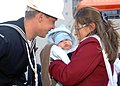 US Navy 101223-N-5292M-174 Boatswain's Mate 3rd Class Jonathan Levai greets his wife and four-month-old son during a homecoming celebration for the.jpg