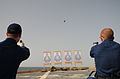 US Navy 111022-N-XQ375-547 Operations Specialist 3rd Class Dustin Reeves, left, and Lt. j.g. Jason Coyle fire 9mm pistols during a weapons qualific.jpg