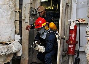 US Navy 120210-N-ZZ999-006 Senior Chief Ship's Serviceman Mario S. Rivers directs Machinist's Mate 3rd Class Mark J. Ligon towards a fire during a.jpg