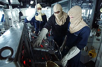 USS Anzio (CG-68) - U.S. Navy sailors in flash gear man the helm during a general quarters drill aboard USS Anzio in June 2002.