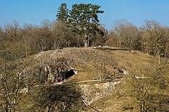 Photographie en couleurs d'une colline percée de deux ouvertures, recouverte d'un tapis herbeux, d'arbres et de roches affleurantes, un étroit sentier aménagé d'un banc visible à mi-hauteur.