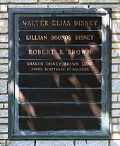 Een grafsteen inscriptie 'Walter Elias Disney', 'Lillian Bounds Disney', 'Robert B. Brown', Sharon Disney Brown Lund as verstrooid in het paradijs'