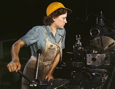 """Rosie the Riveter"" was an iconic symbol of the American homefront and a departure from gender roles due to wartime necessity. WomanFactory1940s.jpg"