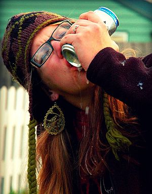 Shotgunning - A woman shotgunning a can of beer