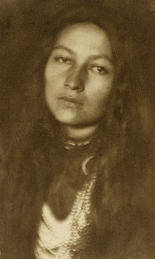Sepia toned image of bust Native American woman looking straight into the camera.