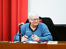 Étienne Balibar in a blue pullover sweater, at a desk with a microphone.