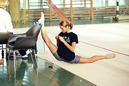 Russian rhythmic gymnast Irina Tchachina stretching in her warm-up before practice. Overspagat.jpg