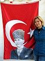 15i6e Aysun Erenalin, Vorsitzende Atatürk Gesellschaft Niedersachsen, hier auf dem Klagesmarkt in Hannover vor türkischer Fahne mit Atatürk.jpg