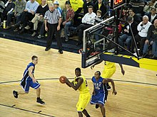 A basketball player in a maize uniform with his back to the basket maneuvers with the basketball. Defenders in light blue uniforms attempt to contest him.