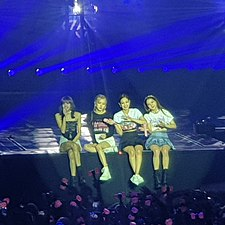 Four members of Blackpink sit on the edge of the stage, waving at fans