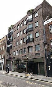 A five storey brick building with a shop on the ground floor and flats above
