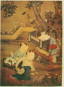 Three young boys sit and watch as a fourth boy dangles puppets from behind a small booth set up in a garden.