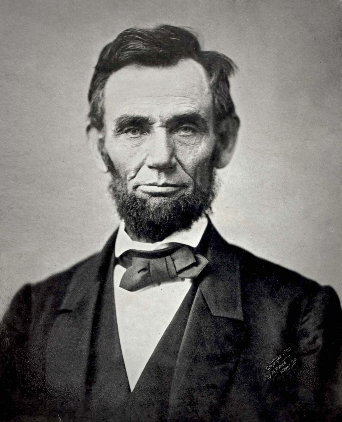 An iconic black and white photograph of a bearded Abraham Lincoln showing his head and shoulders.