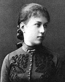 Young woman facing right, wearing high-necked, embroidered dress