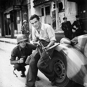 American officer and French partisan crouch behind an auto during a street fight in a French city. - NARA - 531322 - restored by Buidhe.jpg