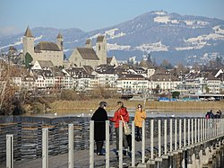 Ansicht von der Holzbrücke Rapperswil-Hurden auf die Altstadt und den Herrenberg in Rapperswil, im Hintergrund der Bachtel 2013-12-01 14-27-41 (P7800).JPG