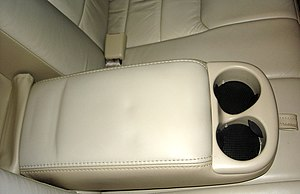Armrest - The armrest in the backseat of a Lincoln Town Car, featuring cupholders.