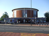 A circular red brick building with concrete roof and glazed screens rises over a lower building