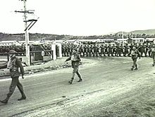 Soldiers march through the gates of a military barracks