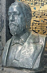 "The bust of Borodin at his tomb in Tikhvin Cemetery. (The visible musical notation on the tile monument in the background shows themes from (1) ""Gliding Dance of the Maidens"" from Polovetsian Dances; (2) ""Song of the Dark Forest""; and (3) the ""Scherzo"" theme from Symphony No. 3.)"