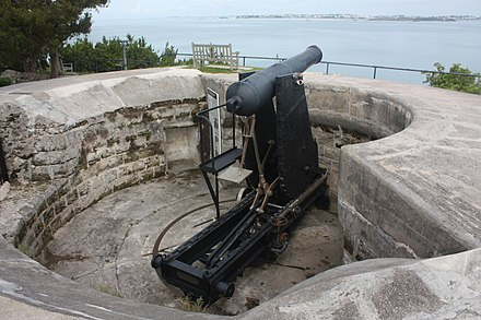British 64 Pounder Rifled Muzzle-Loaded (RML) Gun on a Moncrieff disappearing mount, at Scaur Hill Fort, Bermuda. This is a part of a fixed battery, meant to protect against over-land attack and to serve as coastal artillery. British 64 Pounder Rifled Muzzle-Loaded (RML) Gun on Moncrieff disappearing mount, at Scaur Hill Fort, Bermuda.jpg