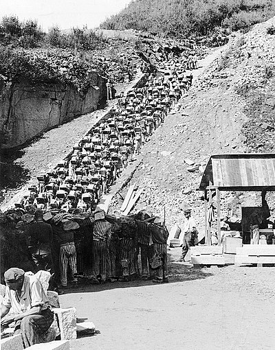 """Stairs of Death"" at Mauthausen-Gusen with prisoners forced to carry a granite block up 186 steps to the top of the quarry. Bundesarchiv Bild 192-269, KZ Mauthausen, Haftlinge im Steinbruch.jpg"