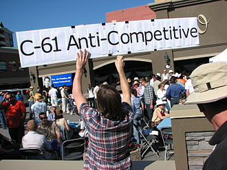 Jim Prentice - An opponent of the proposed Bill C-61 holds up a protest sign at a public breakfast event held during the Calgary Stampede by Canadian Industry Minister Jim Prentice.