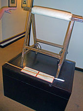 A wooden stand of two triangular portions with a padded brace between them on a black pedestal. A hand points from the left, and a small wooden stick with cotton wrapped around one end is in front.