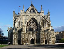 The facade of Exeter Cathedral appears to have been constructed in three layers. In the first layer there is the gable of the cathedral with a traceried window which peeps over the battlements of the second layer. This layer, which is battlemented, includes the lower aisles and a large western window which has within its arch a circle pattern of elaborate stone lace. Across the entire lower front of the building stretches a stone screen with three doors into the nave and the aisles. The screen is tiered with niches containing numerous statues.