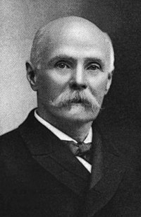 A black and white photograph of an elderly man with a white mustache in a suite and tie
