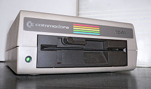 Commodore 1541 - Front view of the second-most common version of the Commodore 1541 disk drive, with open disk slot: this version uses a Newtronics drive mechanism, and the rotating lever is used to engage the drive mechanism with the disk (i.e. to engage the hub clamp and load the disk heads) and to prevent removal of the disk while the mechanism is mechanically engaged.