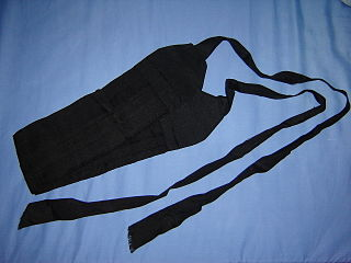 Cummerbund broad waist sash, usually pleated, which is often worn with single-breasted dinner jackets or tuxedos