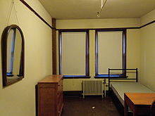 A room with dark floors, brown trim and, from left to right, a mirror hanging on the wall, a dresser, two windows with their shades drawn fully, a radiator, a bed, and a desk