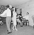 Dansende gastvrouw met een van de gasten terwijl ze een glazen vaas op haar scho, Bestanddeelnr 255-4332.jpg