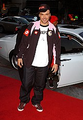 A man standing before a car. He is wearing a white T-shirt and brown coat, with black pants and sneakers