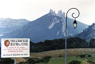 Beaumes de Venise AOC - The Dentelles in the background to a sign touting the Cote du Rhone-Villages wines of Beaumes de Venise.