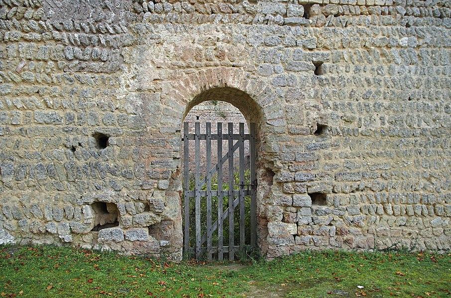 """Doué-la-Fontaine (Maine-et-Loire)  Aula Carolingienne (Xe siècle).   Cet édifice fut découvert en 1966. La municipalité avait décidé d'araser une butte de terre appelée """"Motte de la Chapelle"""". On exhuma alors les ruines d'un bâtiment,  d'environ 23 mètres de long sur 17 mètres de large, et d'une hauteur de 5 mètres.   La recherche archéologique nous révèle que la structure découverte correspondrait à une aula* carolingienne construite dans les années 900.   Le bâtiment, alors en possession des vicomtes d'Angers, les Foulques,  a été incendié vers 930-940, sans doute lors d'une guerre entre les comtes d'Anjou et les comtes de Blois.   Suite à cet incendie, une surélévation des murs transforme l'édifice en donjon. Les portes sont murées et d'autres portes ouvertes à 5 mètre de hauteur. L'exemple exceptionnel de Doué montre que le passage de la simple habitation princière, la aula, au donjon rectangulaire défensif, a pu être une simple transformation """"naturelle"""".   Début XIe siècle, l'aula est enterrée sur une hauteur de 5 mètres et l'ensemble transformé en motte castrale sur laquelle on érigea une fortification en bois.  Un fossé d'une quinzaine de mètres de large et profond d'environ 5 mètres  fut creusé autour de la motte. La aula constituait alors une sorte de cave sous la motte.   Le bâtiment est percé de deux portes, une sur la façade ouest et une plus petite sur la façade sud. Des cavités rectangulaires dansl'épaisseur des murs suggère que de grosses poutres pouvaient servir à barricader les portes.   Le puits est contemporain de l'aula. Il traverse une ancienne carrière à sarcophages qui servit ensuite de dépendance souterraine au palais.     L'aula carolingienne était la grande salle seigneuriale du palais carolingien qui comprenani aussi la """"capella"""", la chapelle, et la """"camerae"""", la partie domestique. www.ville-douelafontaine.fr/fr/decouvrir/histoire-et-patr...  www.persee.fr/doc/bulmo_0007-473x_1977_num_135_2_5585  www.histoire-pour-tous.fr/tourisme/102-fra"""