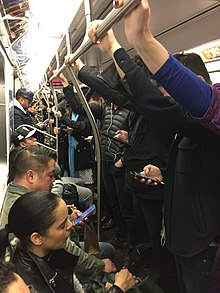 The Q train filled with commuters, many within one inch of each other. Several commuters are seen using smartphones; others are holding on to the train while standing.